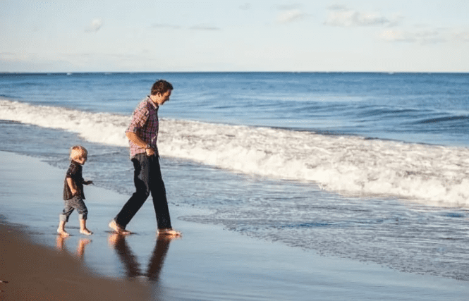 Dad and child walking on the beach